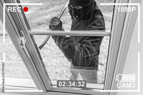 Cuadros en Lienzo CCTV view of burglar breaking in to home through window