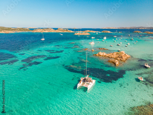 Drone aerial view of catamaran sailing boat in Maddalena Archipelago, Sardinia, Italy. Maddalena Archipelago is composed of Razzoli, Santa Maria and Budelli islands.