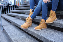 Fashioned Couple Sitting On The Stairs Jeans And Brown Boots Close Up