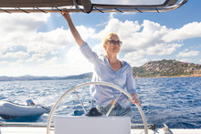 Attractive Blond Female Skipper Navigating The Fancy Catamaran Sailboat On Sunny Summer Day On Calm Blue Sea Water. Luxury Summer Adventure, Active Nautical Vacation.