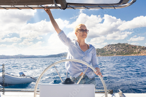 Papiers peints Nautique motorise Attractive blond female skipper navigating the fancy catamaran sailboat on sunny summer day on calm blue sea water. Luxury summer adventure, active nautical vacation.