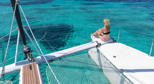 Foto Woman in bikini tanning and relaxing on a summer sailin cruise, sitting on a luxury catamaran in picture perfect turquoise blue lagoon near Spargi island in Maddalena Archipelago, Sardinia, Italy