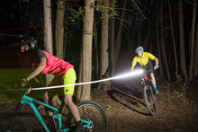 Man And Woman Riding Mountain Bikes At Night With Lights.