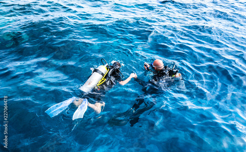 Fototapeta diving instructor holding a disciple's hand in blue water obraz