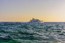 White Pleasure Boat With People In The Open Sea On The Horizon In The Evening