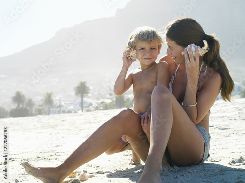Obraz na plátně Mother and son in swimwear sitting on sandy beach listening to sea shells on sum