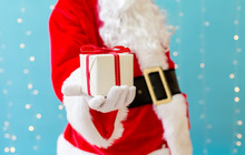 Santa Holding A Small Christmas Gift On A Shiny Light Blue Background
