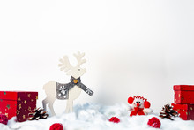 A Christmas Card With A Wooden Reindeer, Red Gifts And A Plush Snowman With A White Copy Space Background