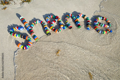 Fotografía  Shame message made from found plastic trash bottle tops on a smooth sand beach