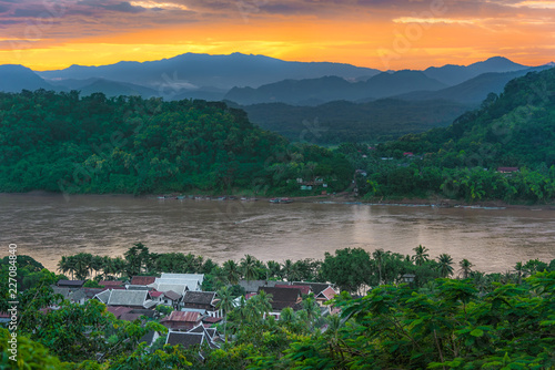Luang Prabang in Laos with mekong river with moutains, beautiful sunset houses of the village and a river surrounded by green trees and nature