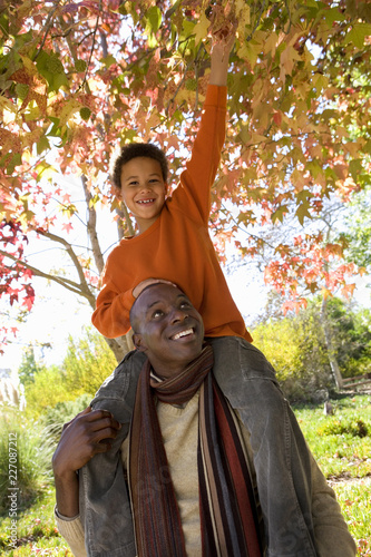 Fotografie, Obraz  Smiling father with son on shoulders in park in autumn at camera