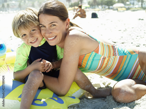 Fotografie, Obraz  Smiling mother and son on sandy beach hugging on beach vacation