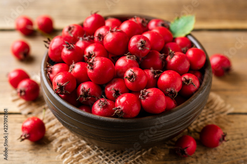 Crataegus or hawthorn berries in ceramic bowl on rustic wooden background Fototapeta