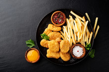 Chicken Nuggets And French Fries With Various Sauces On A Black Background. Top View