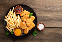 Chicken Nuggets And French Fries With Various Sauces On A Wooden Background. Top View