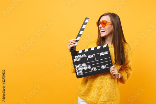 Obraz Laughing young woman in orange heart eyeglasses looking aside and holding classic black film making clapperboard isolated on yellow background. People sincere emotions, lifestyle. Advertising area. - fototapety do salonu
