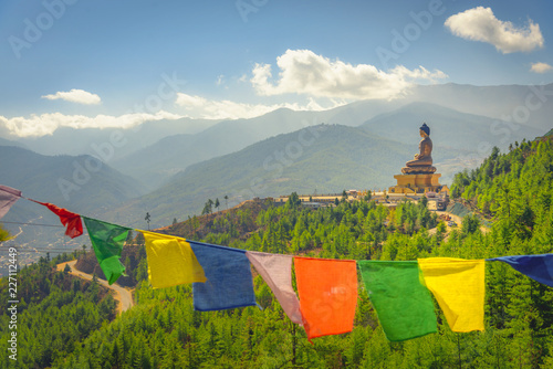 Photo Paro Buddha with prayer flags in foreground and the valley in the background