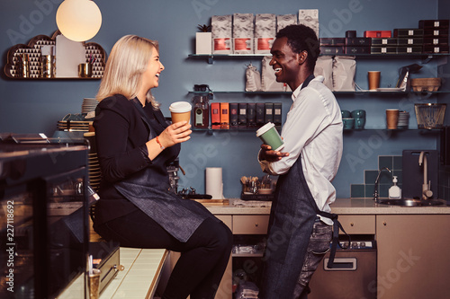 Foto  Two young multiracial baristas relaxing after work laughing and talking together at the trendy coffee shop