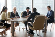 Diverse workers use gadgets at business meeting in modern office, employees browsing internet or check email holding devices, partners or colleagues busy with smartphone and laptop during negotiations