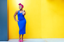 Woman In Blue Dress Standing In Front Of Yellow Wall