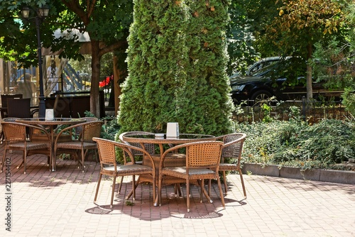 Staande foto Marokko brown wicker table and chairs on the sidewalk near the green spruce park