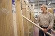 Mature man selecting timber for DIY project in hardware store