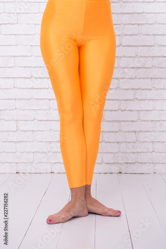 e602f328b dancing ballet position of feet. orange. practicing in ballet studio. sport  wear fashion. woman in orange leggings on legs. Adorn your Hobby with Dance.