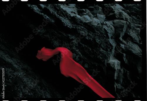 Fotobehang Stof Red fabric along dark rocks