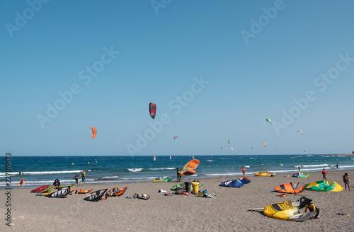 Many kitesurfer and windsurfer on ocean at surfer beach El Medano, Tenerife