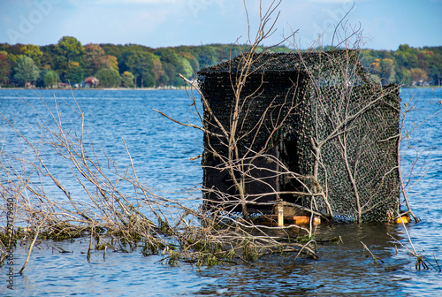 duck blind camouflaged with dark mesh and tree branches in lake water