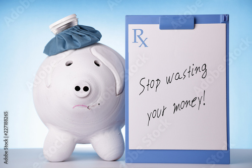 Fotografie, Obraz  Big piggy bank with ice bag next to a prescription that reads: Stop wasting your