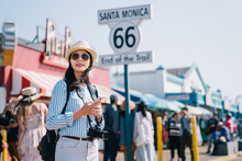 Tourist Standing Next To The Sign Of Santa Monica