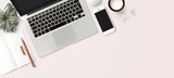 modern header / hero image or banner with laptop computer, smartphone, air plant, open notebook and feminine accessories on a bright blush background, home office scene, flat lay / top view