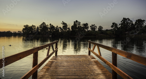 Reddish wooden pier over the lake with calm waters at sunset