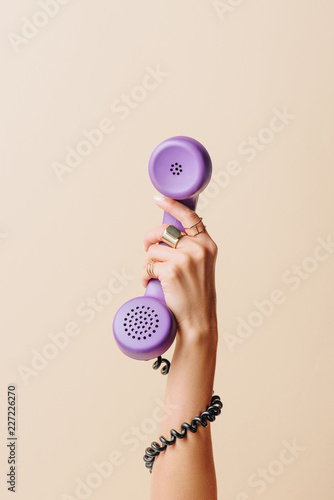 Fotografia  partial view of woman holding purple phone tube on beige