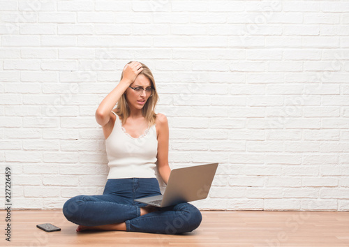 Poster Ecole de Yoga Beautiful young woman sitting on the floor working using laptop at home stressed with hand on head, shocked with shame and surprise face, angry and frustrated. Fear and upset for mistake.