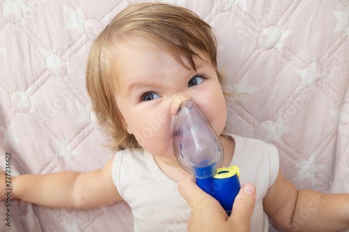 Fényképezés  baby girl sick and don't want to use nebulizer mask making inhalation, respiratory procedure by pneumonia or cough for child,  inhaler, compressor nebulizer, health care