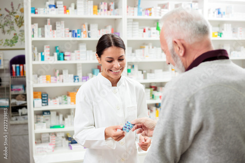 Photo sur Toile Pharmacie Medicine, pharmaceutics, health care and people concept - happy pharmacist giving medications to senior man customer