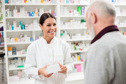 Fotobehang Apotheek Medicine, pharmaceutics, health care and people concept - Happy female pharmacist giving medications to senior male customer
