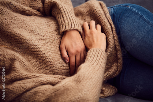 Canvastavla Woman having stomach issues / problems while lying on the couch.