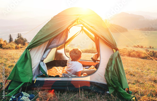 Boy rest in camping tent and enjoy with sunset light in mountain valley