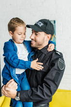 Handsome Young Father In Police Uniform Carrying His Little Son