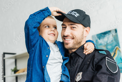 Fototapeta close-up portrait of smiling young father in police uniform carrying his little