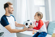 cheerful man and son with football ball at home