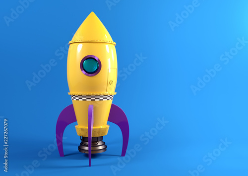 Fotografia, Obraz A retro yellow toy spaceship rocket set against a blue background ready to launch