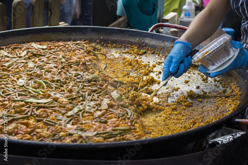 Street food: cooking and serving paella, traditional spanish rice dish