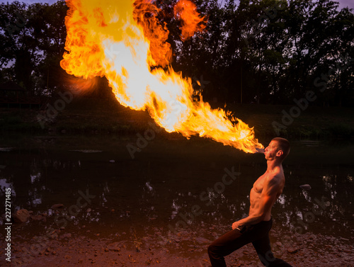 Leinwand Poster Man fire-eater blowing a large flame