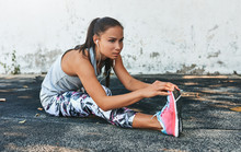 Fitness Young Woman Stretching And Listening The Music On Earphones Before Outdoors Against Concrete Wall. Athletic Female Stretch After Workout Outside. Sport And People Concept