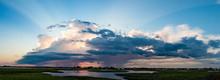Summer Raincloud Over The Marsh With Sun Setting