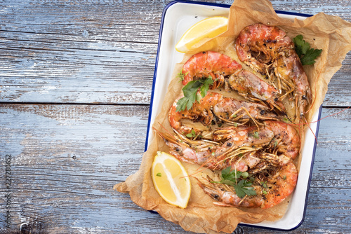 Traditional fried black tiger prawn with lemon as top view in a white casserole on a wooden blue board with copy space left